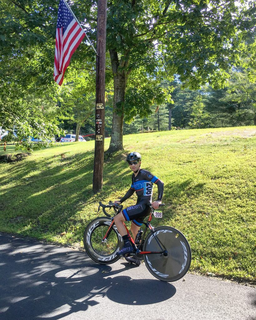 Cyclist standing under American Flag