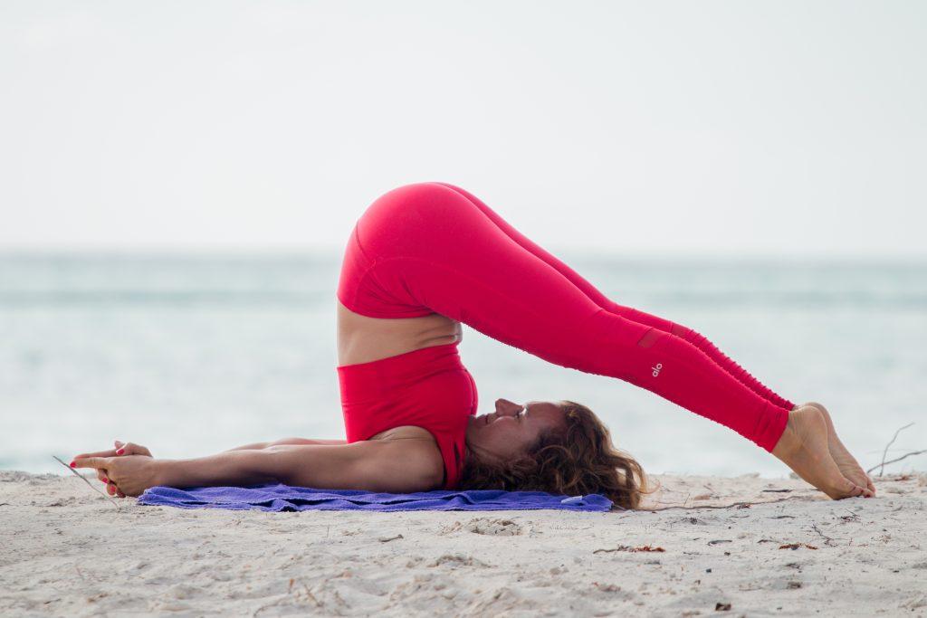woman doing yoga on a beach